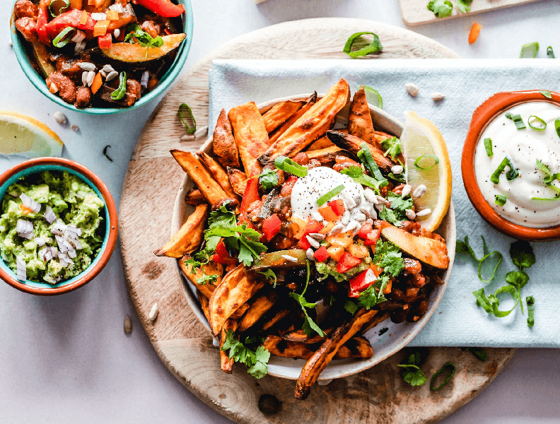 Huge bowl of sweet potato wedges with salsa, guac and sour cream